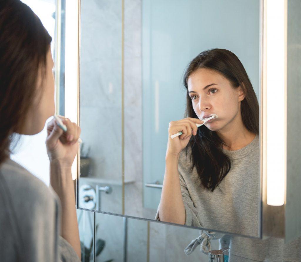 Woman brushing her teeth - weird pregnancy symptoms